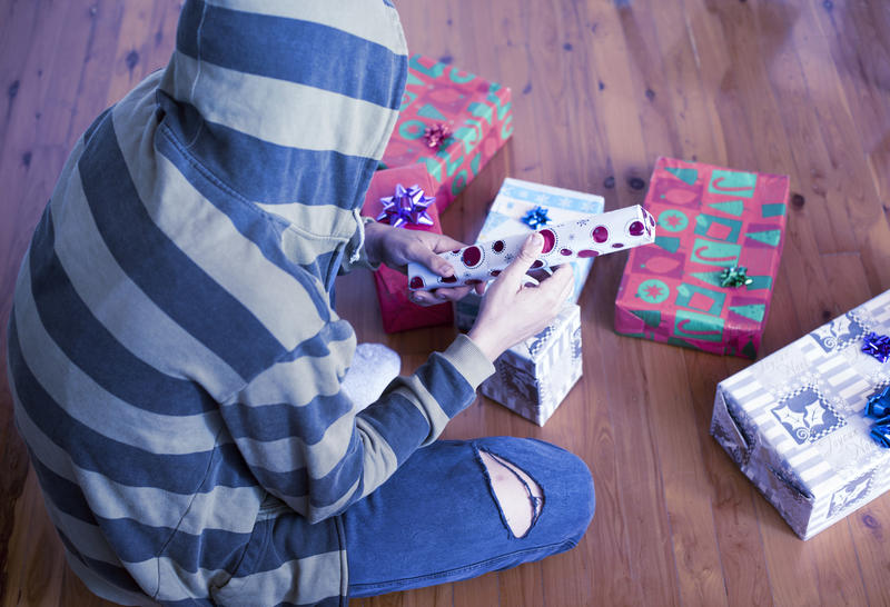 Person wearing a hooded top sitting on the floor opening Christmas gifts on Xmas morning viewed high angle