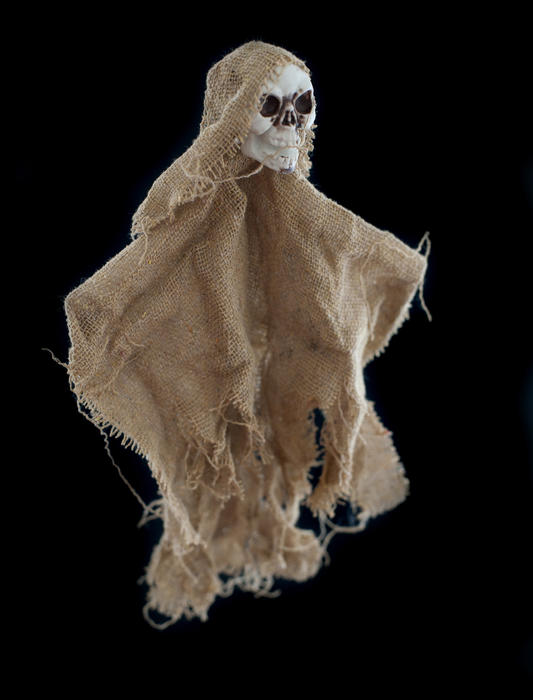 Spooky single burlap Halloween skeleton doll over black background for theme about ghosts