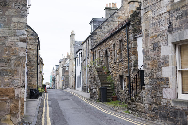 Empty narrow paved road between old stone houses in the town of Saint Andrews, Scotland, Europe