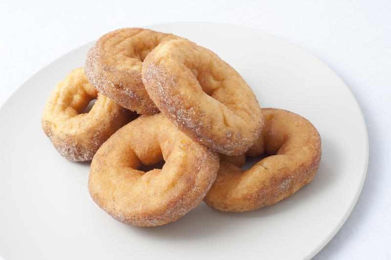 Plate of fresh ring donuts or doughnuts sprinkled with sugar for an unhealthy, but tasty, breakfast