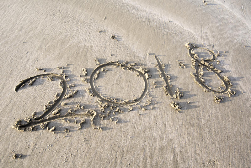 Concept of a summer holiday by the beach, the year 2018 written in sand