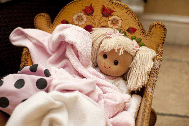 Cute little blond doll in a crib wrapped in a soft pink blanket in a kids playroom , close up high angle view