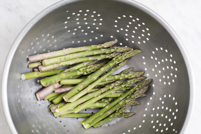 Washing healthy fresh green asparagus spears in a metal colander viewed from above