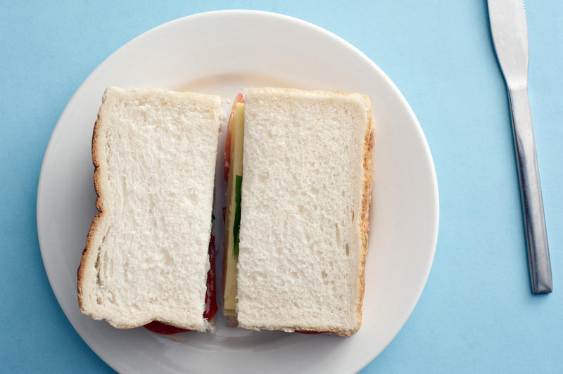 Above view on white bread sandwich in round plate with table knife beside it over blue background