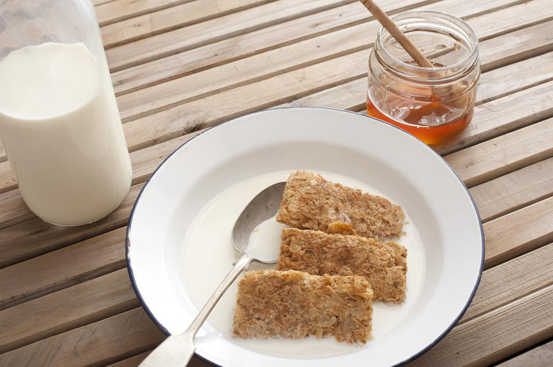 Wholewheat breakfast cereal served in a bowl with milk and honey on a slatted wooden table, high angle view