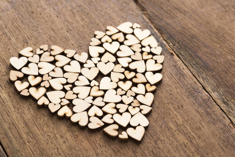Close-up pile of craft wooden hearts cut of unpainted plywood formed in shape of bigger heart over lacquered table surface, love concept