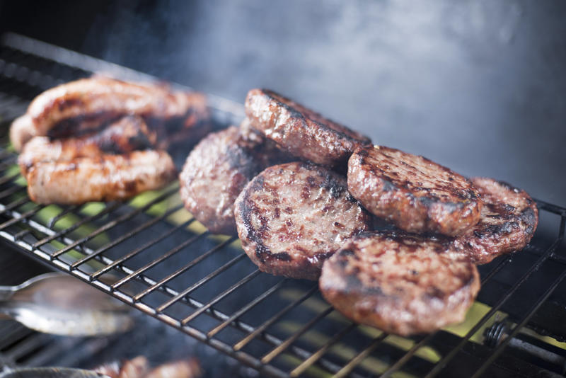 Beef burger patties and sausage on a BBQ grilling over the hot coals with smoke in a close up view