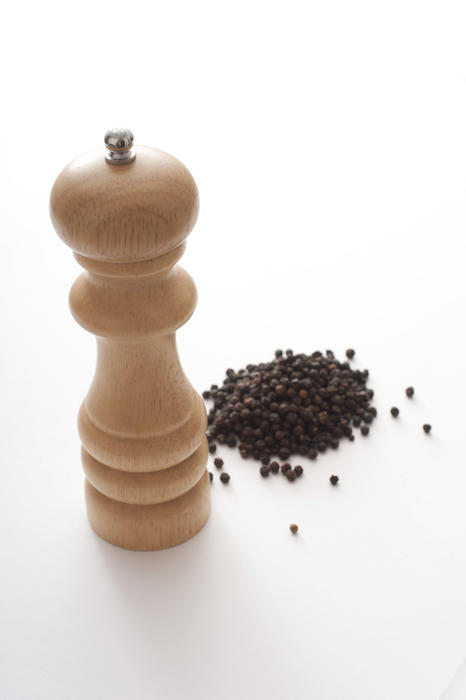 Heap of black peppercorns with a wooden pepper mill or grinder over a white background with copy space