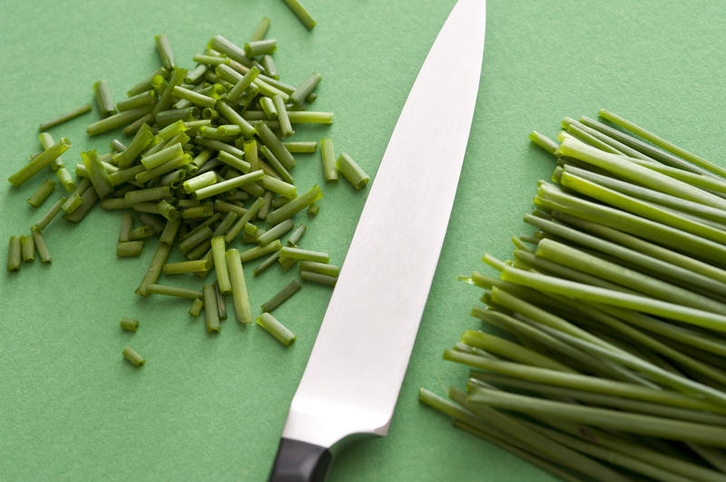 A close up of a sharp knife and chopped chives on a green background with copy space.