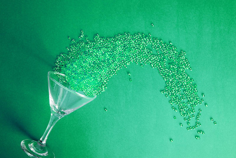 Green martini cocktail party background concept on green with a tilted glass and spray of sparkling spilling beads with copy space