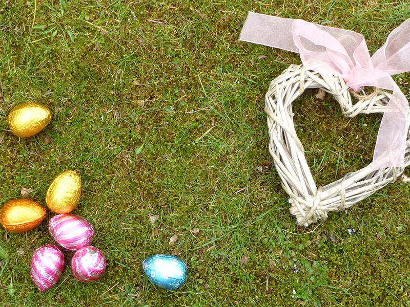 Chocolate Easter eggs in colored foil and wicker heart with pink ribbon, sitting on the ground with fresh green grass. Holiday background concept with copy space