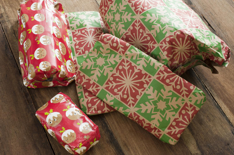 Pile of colourful gift-wrapped Xmas presents on a wooden floor read to celebrate on Christmas morning in a close up view