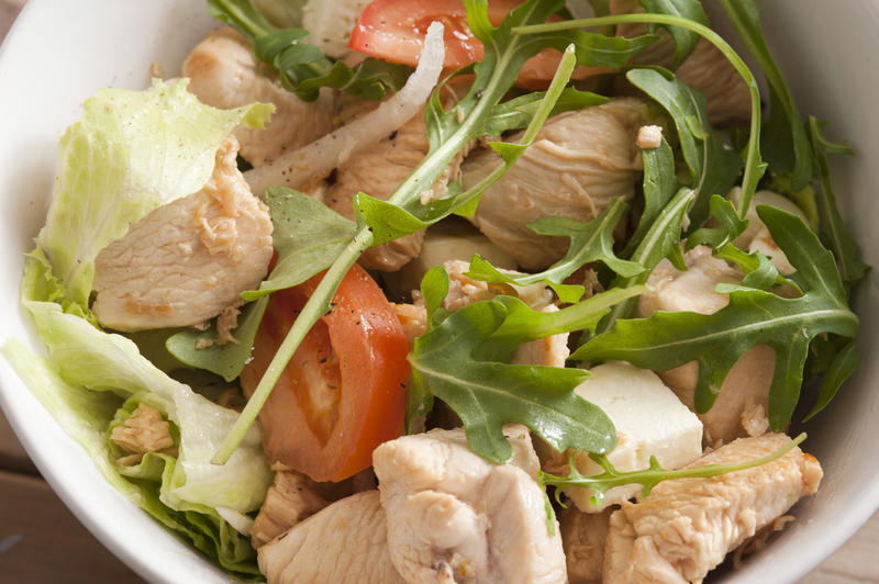 Healthy salad with chicken, tomatoes and arugula, viewed from above in close-up