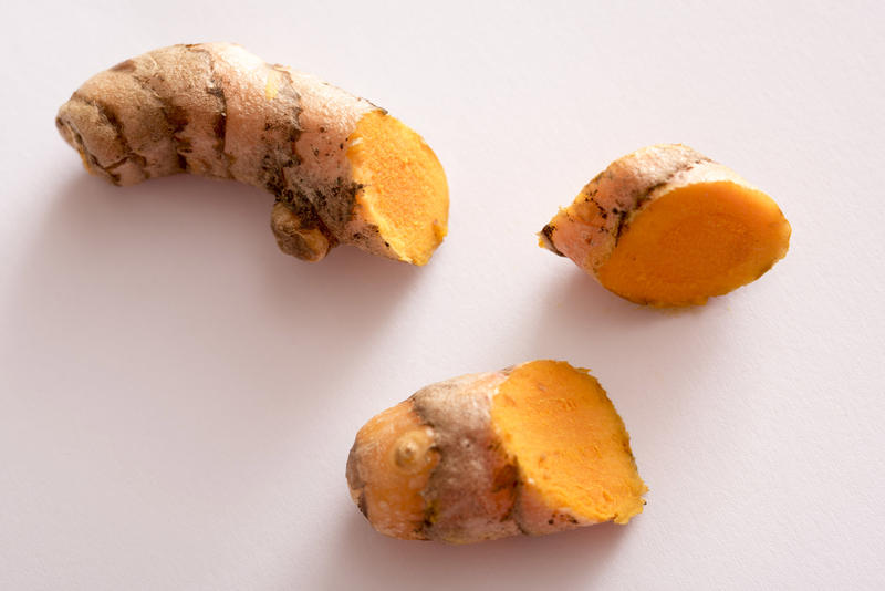 Pieces of sliced turmeric in close-up on white surface, viewed from above