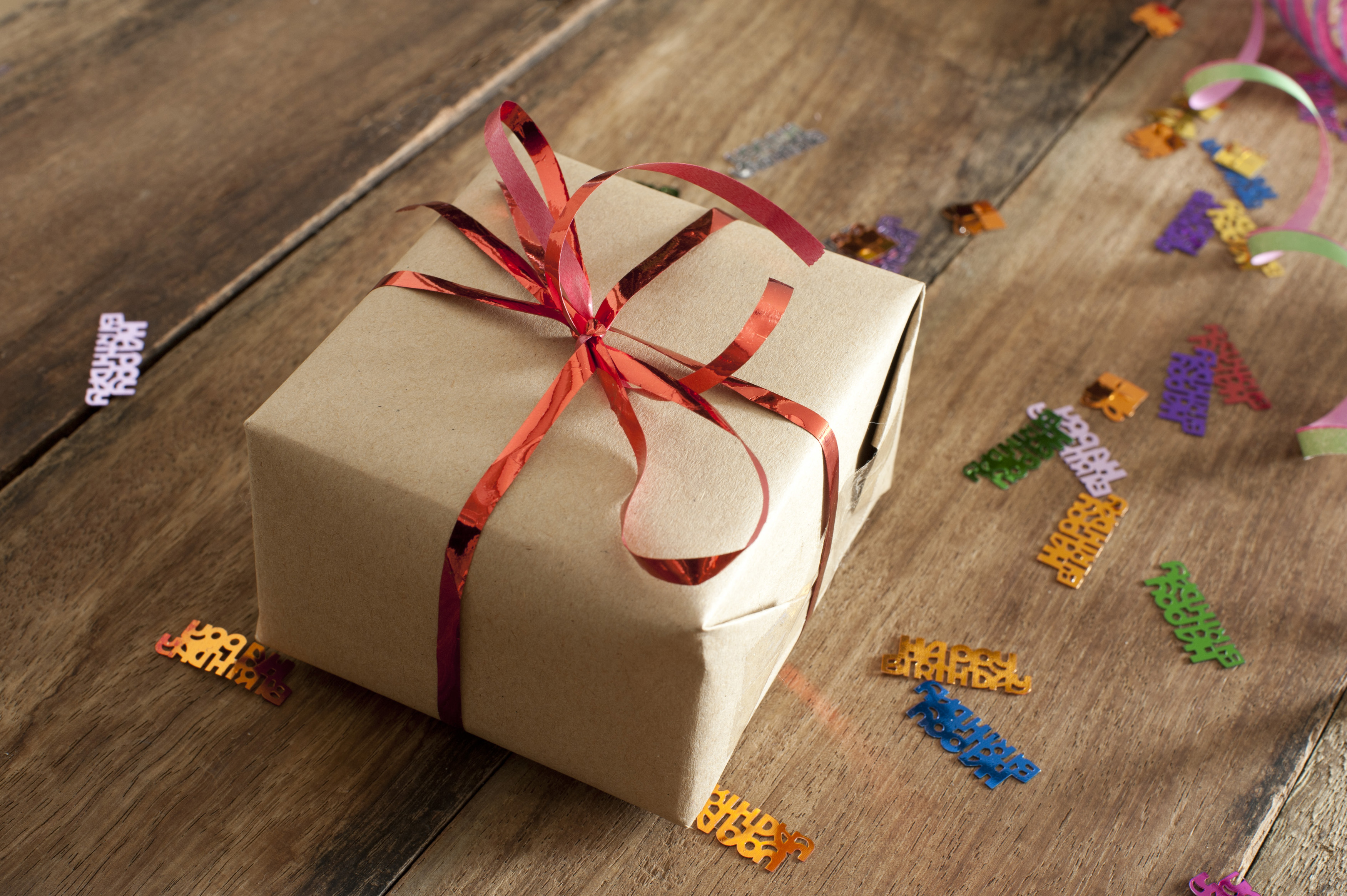 Free stock photo 11433 birthday gift box on the table with confetti brown birthday gift box with red ribbon placed on a wooden table with confetti negle Image collections